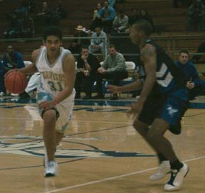 SETTING IT UP ? Falcons´ point guard Ryan Reyes (31) dribbles the ball downcourt against Fullerton.