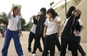 Sara Manson teaches Kyoko Kanagawa, Asuka Kamo and Mayuko Morita basic dance skills at the athletic training session.