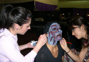 Stage make-up students, Mary Ann Boice and Adriana Torres, assist in putting on make-up for one of Knott's monsters.