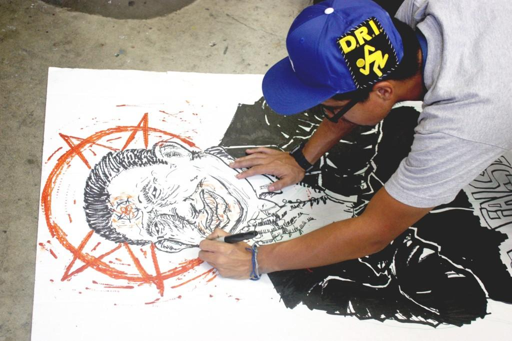 Animation major Galileo Gonzalez adds more definition to his caracture oh Luis Artiga, former Bell councilman. Gonzalez' inspiration for the piece came from the pastor's alleged involvement in a tax-dollar embezzlement scheme.