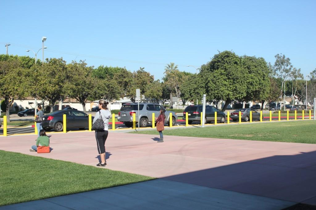 Students wait for cars to arrive by the new student drop-off zone. The new zone was constructed to improve safety and help decrease traffic congestion.
