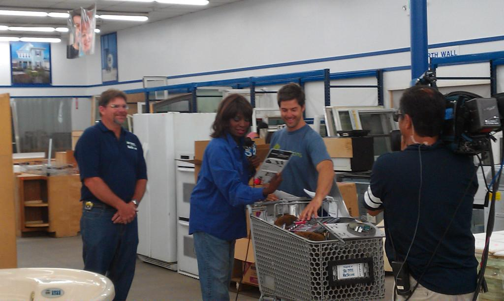 ReStore manager Scott Lee (left), reporter Gayle Anderson (center) and consultant Darren Moore film a live segment for KTLA 5 on Aug. 16. Habitat for Humanity's Norwalk ReStore just reached its first anniversary this month.