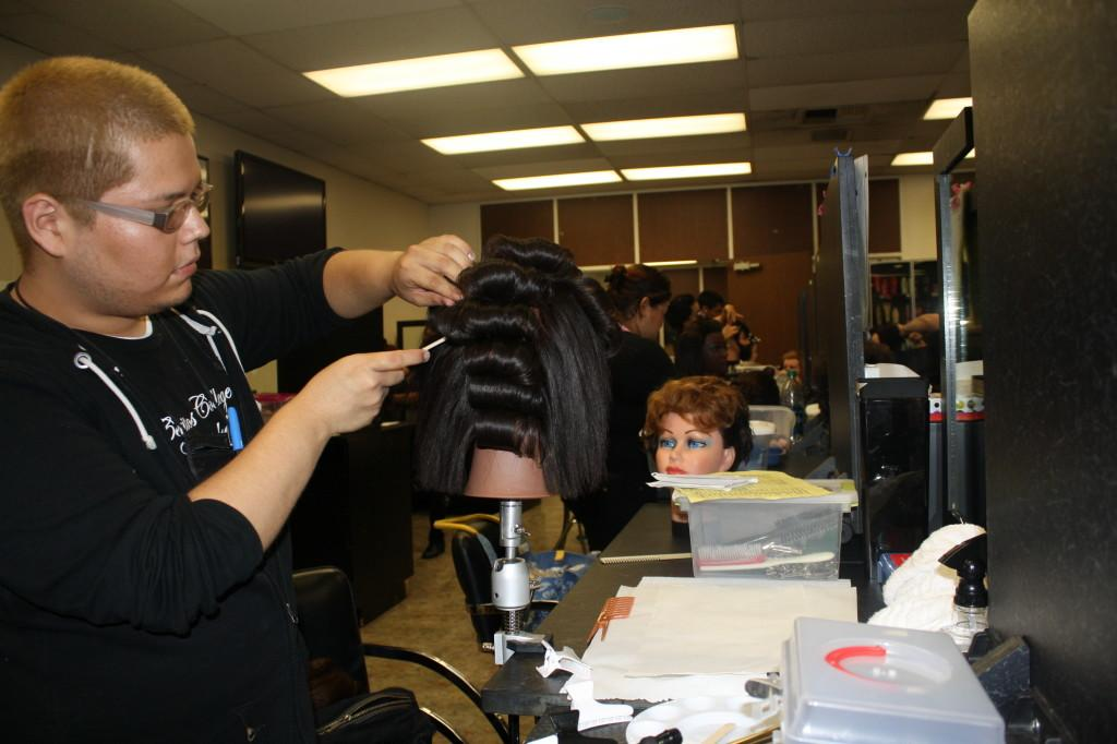 Liberal arts major Edgar Zepeda is working on his mannequin for cosmetology. The Cosmetology Department offers Cerritos students certificates in cosmetology and through the Esthetician Program.