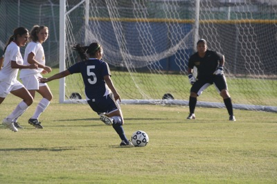 Freshman Midfielder Julissa Castaneda takes a shot against Taft College goal keeper Lesli Aviles in the second half of the game Friday. The Falcons went on to win the game shutting out the Cougars with a score of 3