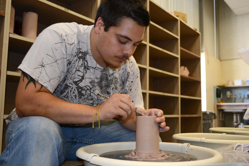 Ron Feese, undeclared major, trims clay for a project to make a cylinder. Feese, a third semester ceramics student, said he is trimming the excess clay to make his completed project lighter in weight.