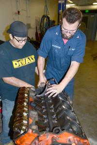 Christina Espinoza, left, automotive business management major, assists Paul Woodrome, political science major, remove a component from the project truck's engine. Four classes in the automotive technology program will share the work on the project truck.