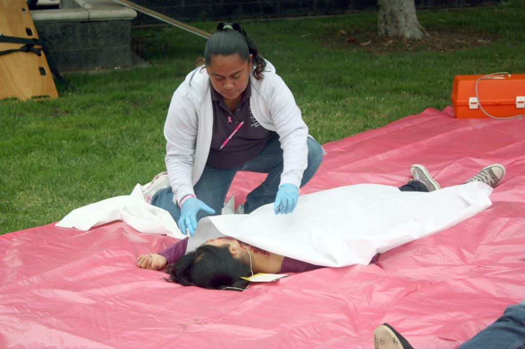 Student Health Services Administrative Assistant Ana Flores assists a student who volunteered as an earthquake victim. Cerritos College took part in the annual