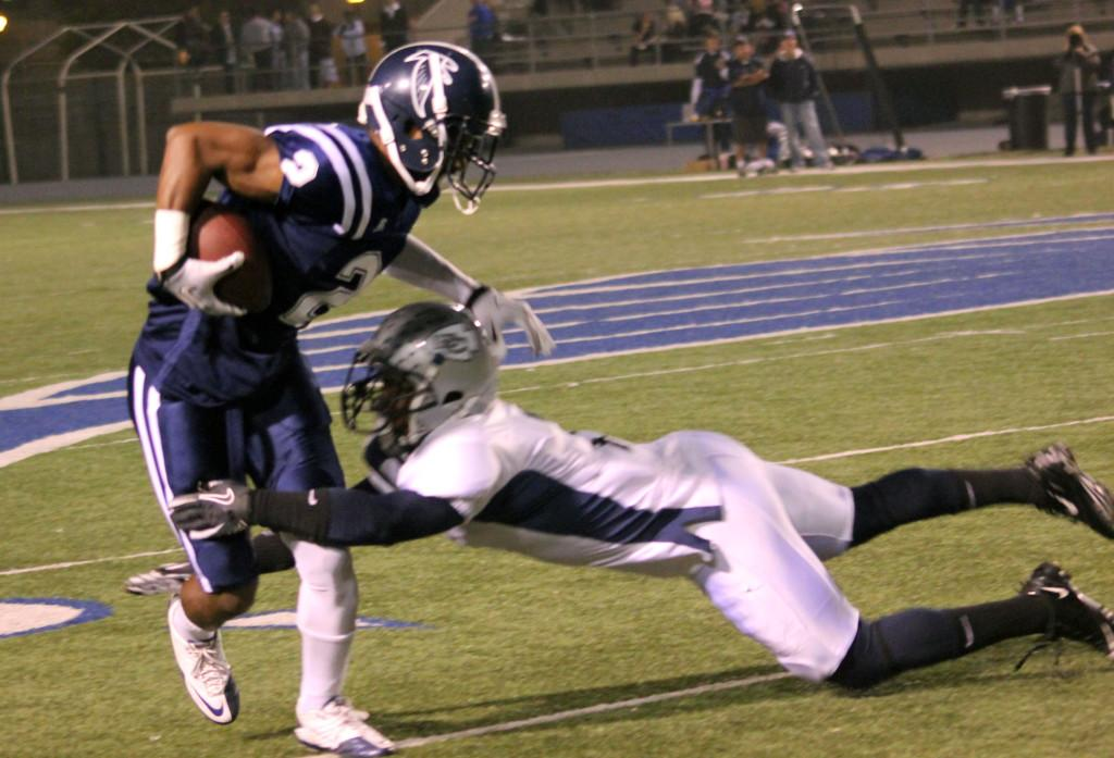 Falcons wide receiver Lindsey Anderson (left) is being tackled by an El Camino College defender (right) during the Cerritos College football team's 42-21 victory at Falcon Stadium on Saturday. Anderson had 52 yards on five catches.