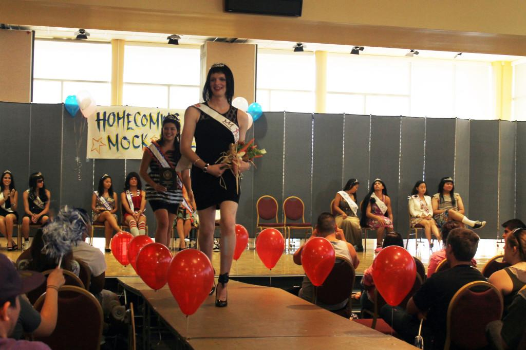 Mock rally winner Justin McIntyre walks on the stage with Homecoming Court candidate Raquel Ramirez. McIntyre won the contest impersonating Ramirez.