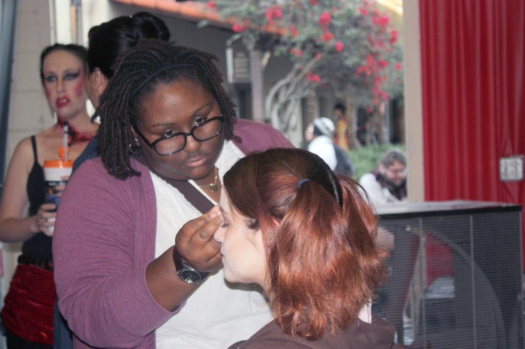Theater major Candace Montgomery assists in putting makeup on Halloween Haunt monster Molly Bennett. Cerritos College Theater students visited the park on Oct. 27 to help makeup artists in creating monsters for the event.