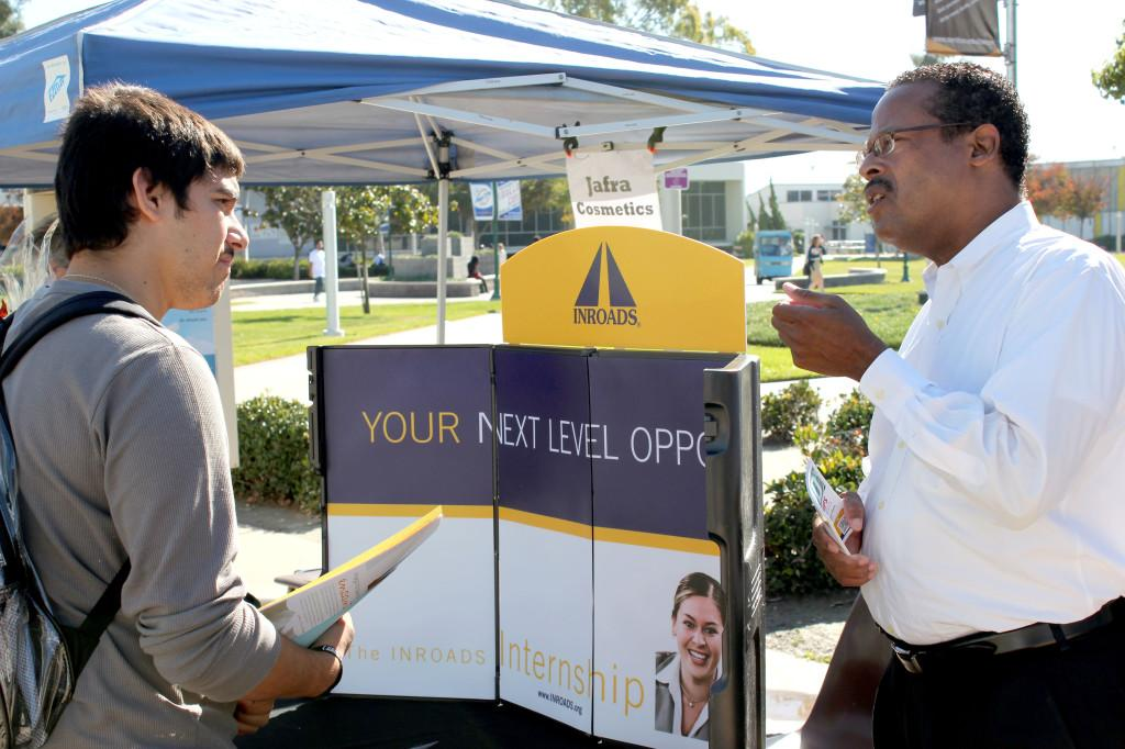 Bryan Barnes (right), a representative from Inroads, a company that prepares students for internships in the workforce, speaks to computer science major Miguel Acosta (left) about his company. Inroads was one of many employers that were present at Wednesday's Job Fair to recruit students for employment.