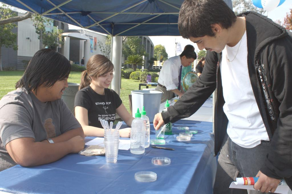 Computer technology major Miguel Acosta (right) holding a gummy worm substance at the chemistry booth in the All Majors Fair with chemistry major Rathana Keo (left) and biology major Emily Ventura. The chemistry booth displayed petri dishes with alginate solution and calcium chloride that formed gummy worm substances.