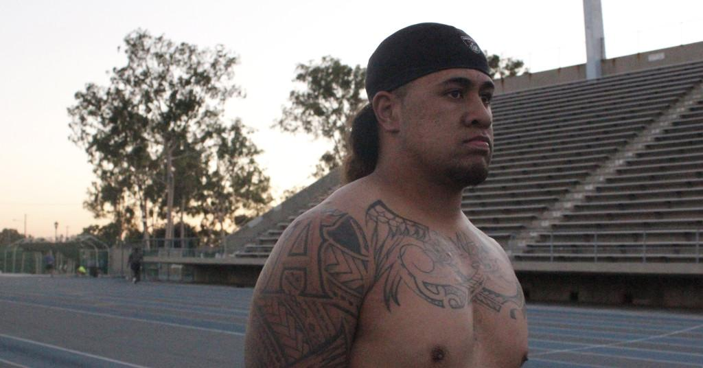 Cerritos College linebacker Donovan Amituanai bares his chest that displays the name of his daughter who is named after his deceased mother. Amituanai is one of several Falcon football players with tribal tattoos.
