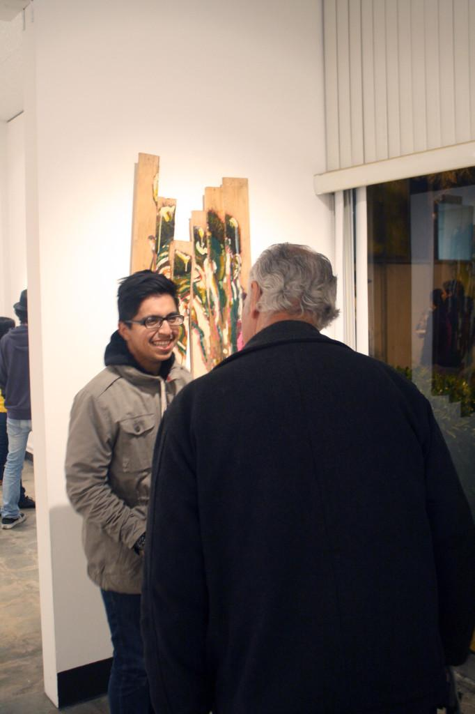 Cerritos College student Galileo Gonzalez (Left) discusses his artwork with a visitor. This is the first piece of artwork displayed in the