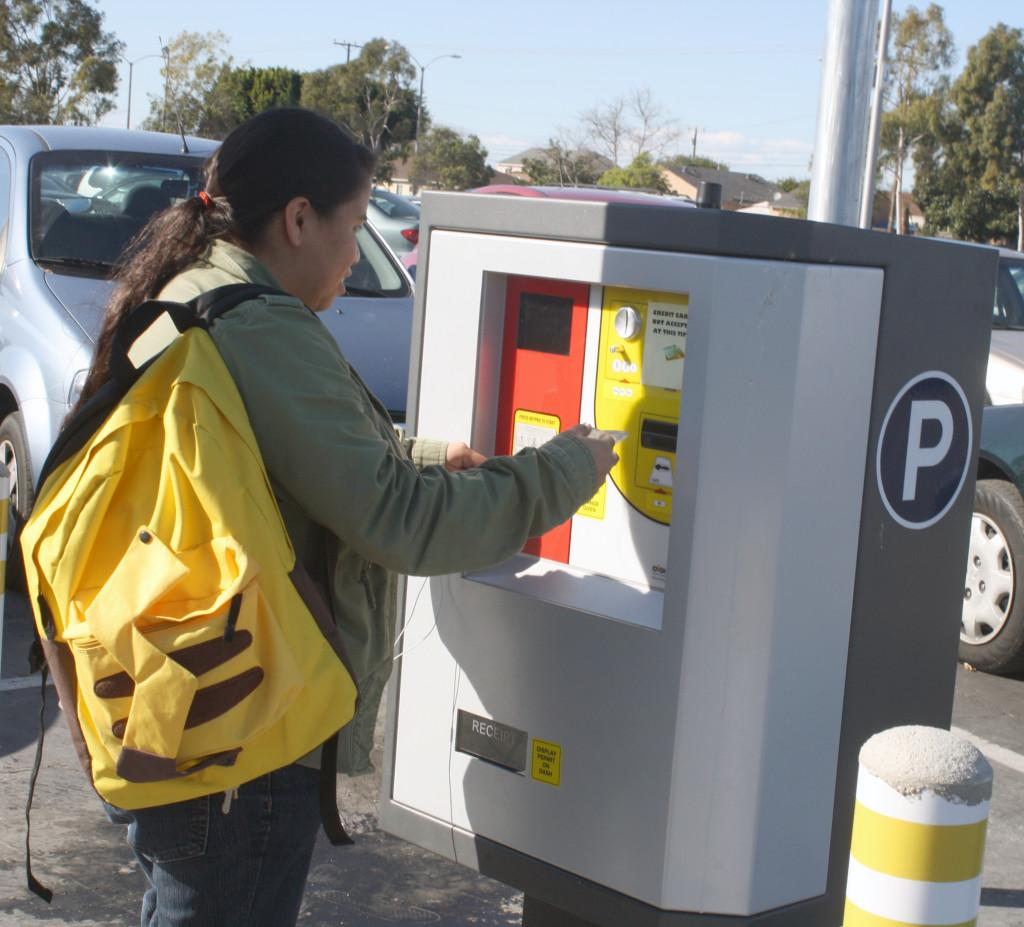 Zoology major Lupe Barron is using a new daily parking permit dispenser in a parking lot at Cerritos College. The dispensers are being used on a trial basis from Feb. 1 until the end of March.