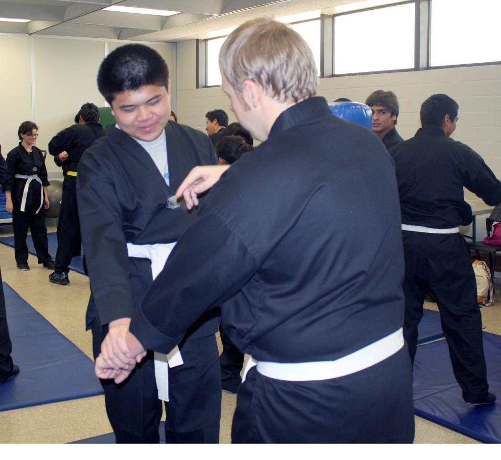 Eric Kim and Shane Glenn Hall, practicing defense methods with the Martial Arts club.