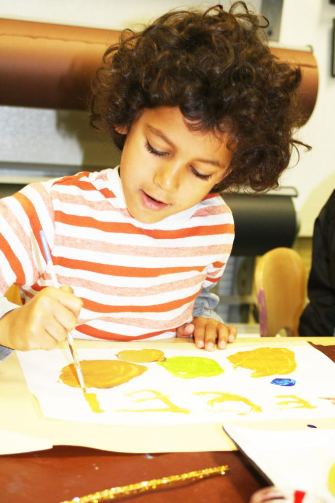 Child Rebel Thomas creates art as he triumphantly signs his name with gold paint. By signing work, children improve on their hand-eye coordination and fine motor skills.