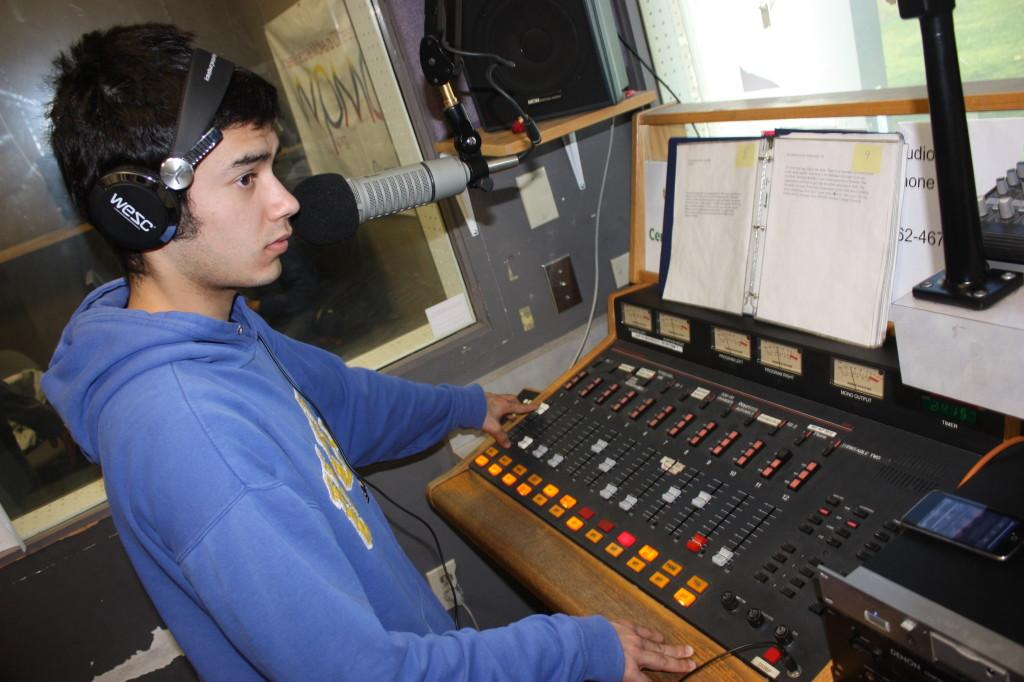 """Radio host for """"The Nonsense Hour,"""" Angel Alcala, working on the control board in the WPMD station on campus. Alcala started his show last semester to play music."""