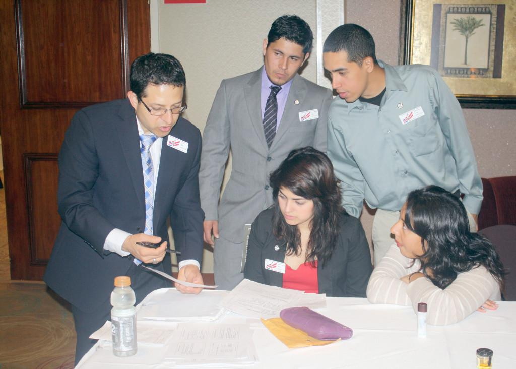 Phi Beta Lambda adviser Professor Jerry Ramos (Far Left) goes over the itinerary for the Business Leadership Conference with several Cerritos College students. The conference lasted two days and offered business workshops and competitions for colleges to compete in.