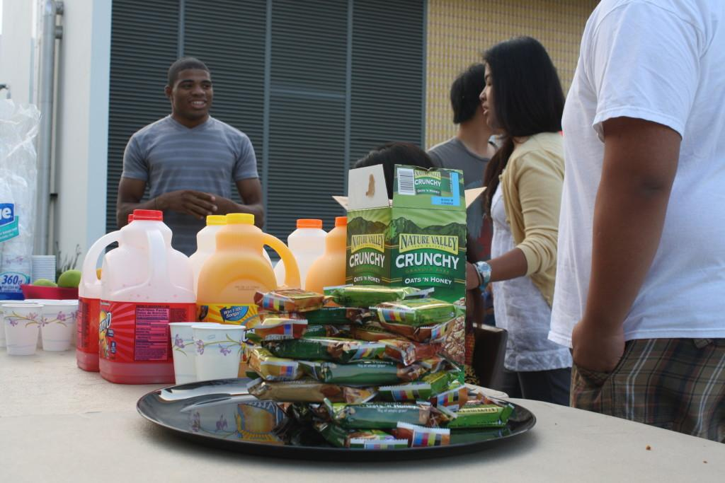 ASCC volunteers converse while they give out free food at the early bird special table.