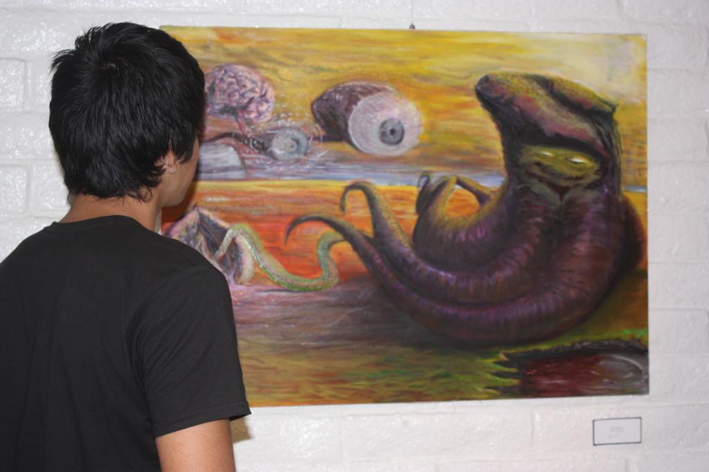 """Art design major Edwin Joshua Espinoza looking at his art work titled """"Squidward"""" at the  Mary Paxon Gallery in Norwalk, Calif."""