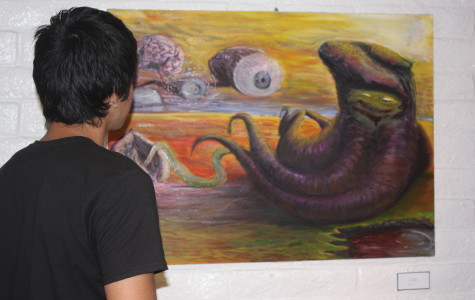 "Art design major Edwin Joshua Espinoza looking at his art work titled ""Squidward"" at the  Mary Paxon Gallery in Norwalk, Calif."