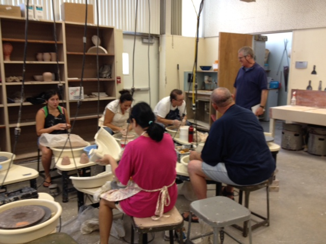 Professor Steven Portigal with students in his ceramics class.