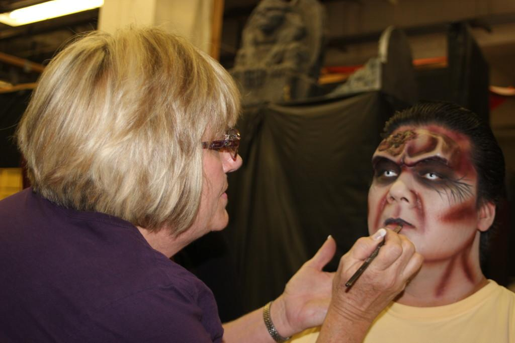 Stage makeup student applying lip color with a brush on one of the ghouls at Knott's Halloween Haunt.