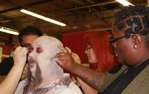 Cerritos College students working together to apply a makeup foundation on one of the models who works a as monster at Knott's Halloween Haunt.