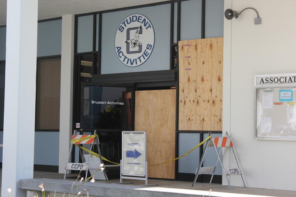 The Student Activities office entrance. Plywood was used to board-up the broken windows and caution signs and tape were placed on and around the affected areas.
