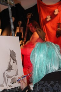 Art major Melissa Duran draws nude model Michael Sscmidt on paper for her life drawing art class. Since the class is on Halloween, the instructor arranged to have a Halloween-themed model to come in to class.