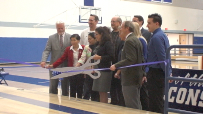 A who's who of the Cerritos College athletic department poses Friday with a huge pair of scissors as the Falcon Gymnasium officially opened.