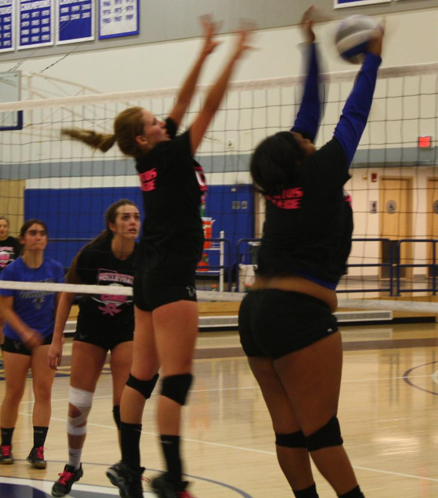 Freshman middle blocker Sara Hickman and freshman outside hitter Tisha Lenon rise up for the ball during practice.