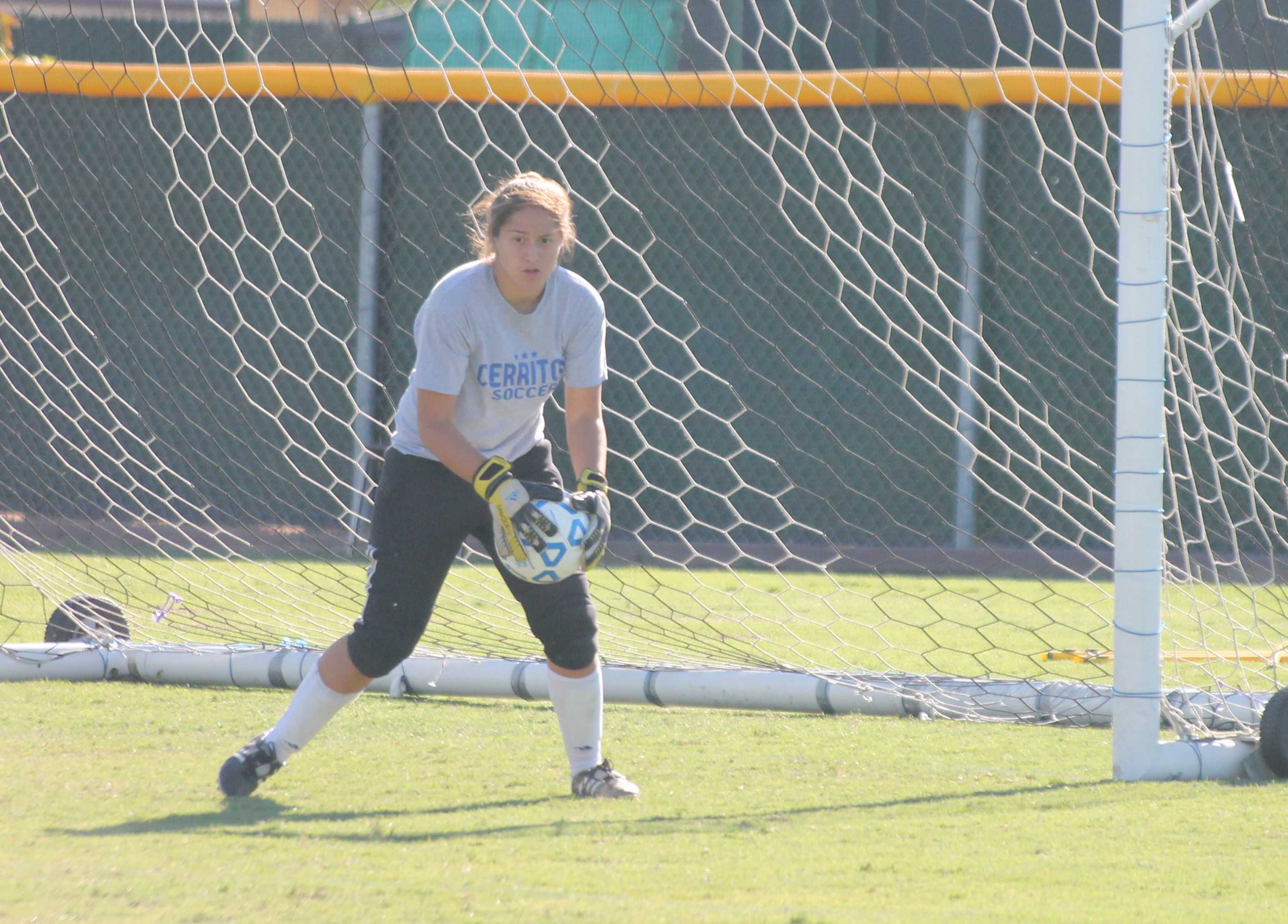 Sophomore goalkeeper Alexis Carrillo intercepts the ball and prevents it from entering the goal while doing a soccer drill during practice. She torn her ACL last season and is getting better as the season goes on.