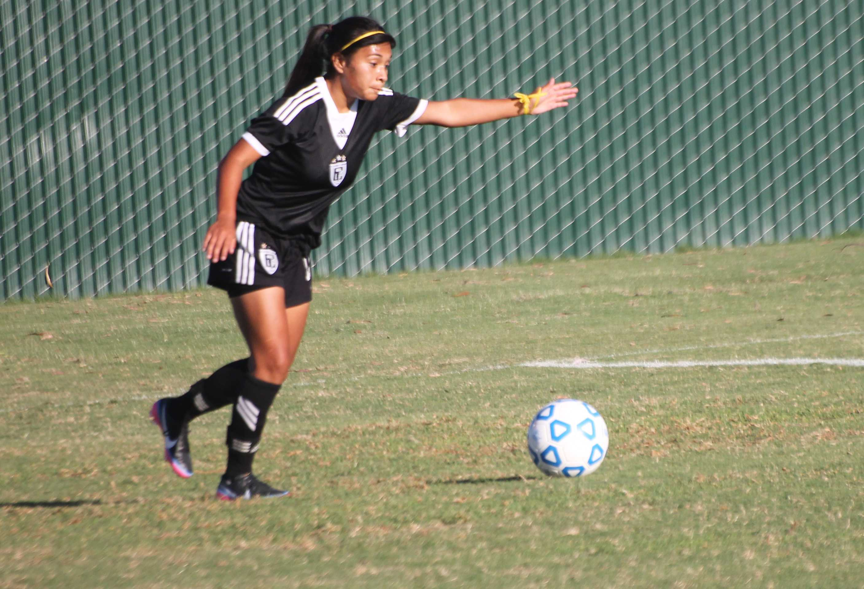 Freshman Carolina Ornelas about to pass the ball toward a teammate.