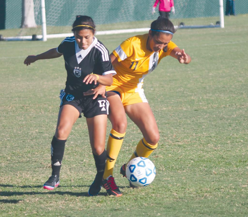 Forward Carolina Ornelas (left) fights Emily Pulido for control of the ball.