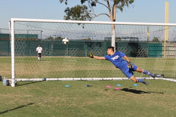Sophomore goalkeeper Benito Gonzalez attempts to block a ball at practice. He has nine saves in the season and has a saving percentage of .692.