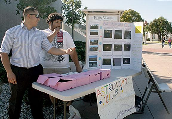 Cerritos College Astronomy Club president Hugh Rivera and treasurer Enrique Rueda stand in front of their table, selling donuts to raise money for their club's field trip to Joshua Tree. The club will visit the site to view stars in a clearer setting.Photo credit: Lauren Gandara.