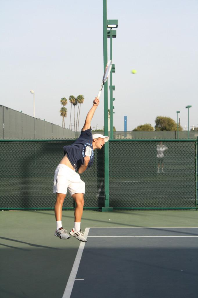 Sophomore Nathan Eshmade prepares a powerful serve during season training for the men's tennis team.Photo credit: Sebastian Echeverry