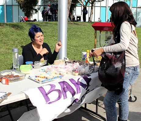 Jennifer Ovalle, president of the Social Equality Club, sitting down by the table and informing a student about the goal of the Social Equality Club and the bake sale.Photo credit: Gustavo Lopez