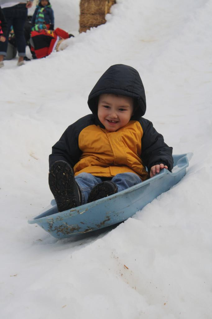 Four+year-old+Joshua+Weir+sliding+down+the+snow+slide+at+the+%E2%80%9CSnowy+Day%E2%80%9D+event+last+Friday.+He+said+he+had+fun+participating+in+all+the+activities.Photo+credit%3A+Sebastian+Echeverry