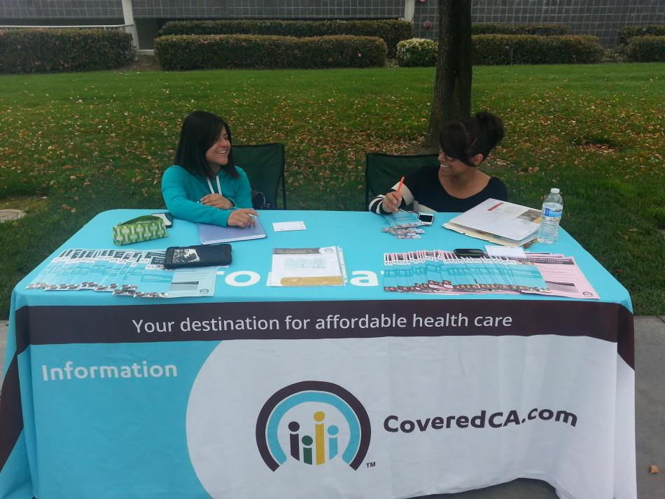 (From left to right) Martha Rodriguez, psychology major, works with Ariday Avellaneda, nursing major, to promote health insurance information to students at Cerritos College. Rodriguez and Avellaneda were hired by USC, which is working with Project HOPE, to spread the word on health insurance. Photo credit: Alexandra Scoville