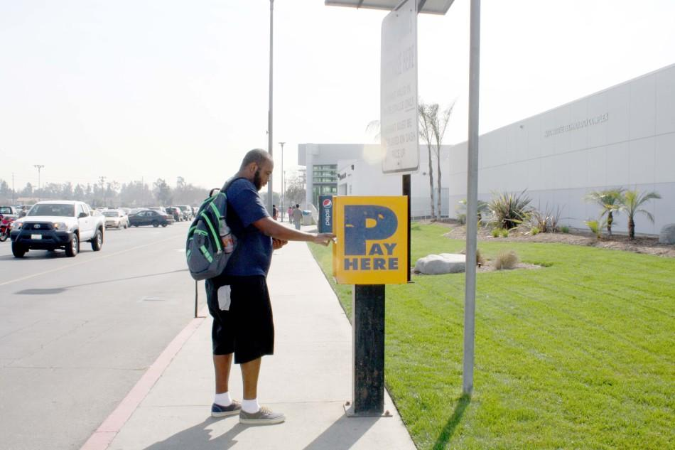 Damani Williams, a computer science major,  paying his one-day parking permit at the Cerritos College parking lot by the Automative Technology Complex building. He is one of many students who believes that there should be more parking machines as the seven machines available are not enough. Photo credit: Amairani Mendez