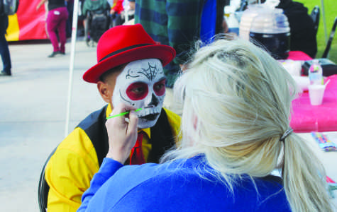 Butch Locsin, an art major, gets his face painted to help promote the Art Society Club's face painting booth. Photo credit: Gustavo Olguin
