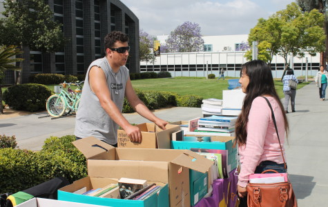 Peter Bouris, computer science major, was a Math Club member who explained to passer-by like Yajara Orozco, a child development major, what books were available for sale and that their goal is to help the Su Casa Foundation.