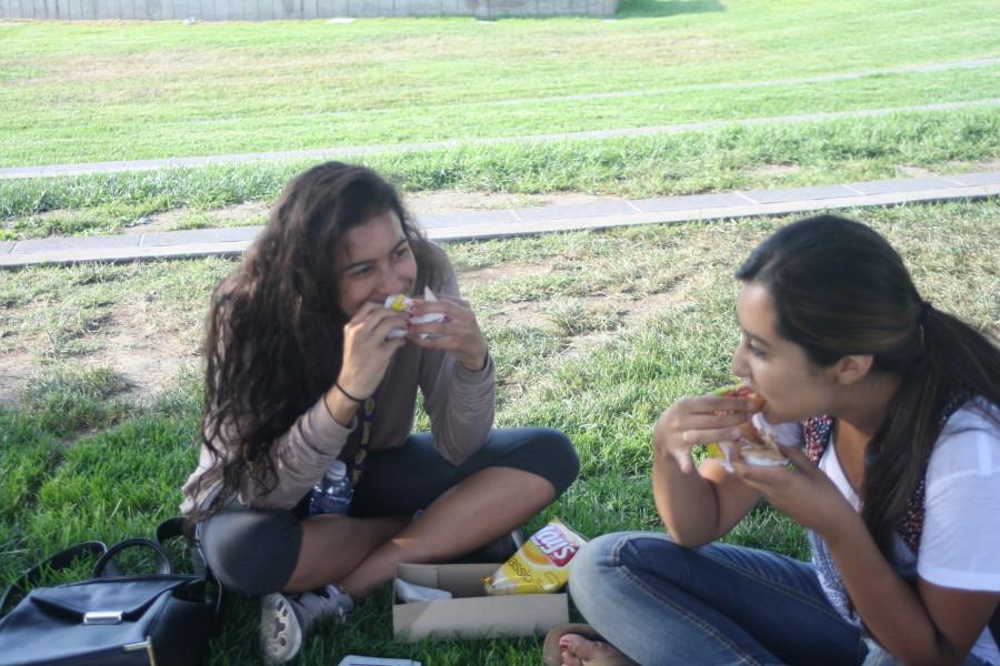 Cindy Manzanares and Kenosha Hawkins, who are both child development majors are taking a delectable bite of their delicious burger.