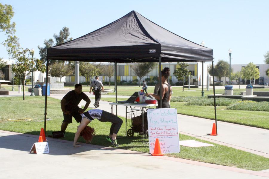 Get Fit club members offer free workouts to Cerritos College students. Members of the club perform yoga poses. Photo credit: Samantha Vasquez