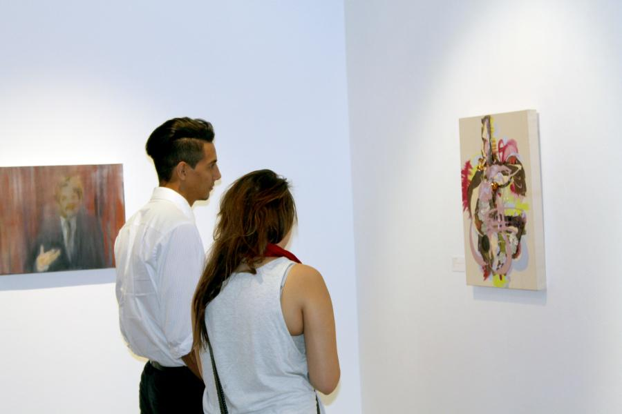 Jose L. Centeno, graphic design major, looks at one of the many pieces of art with a friend in the Savage Sentamentality portion of the art gallery. The art gallery featured artist outside of Cerritos College. Photo credit: Luis Guzman