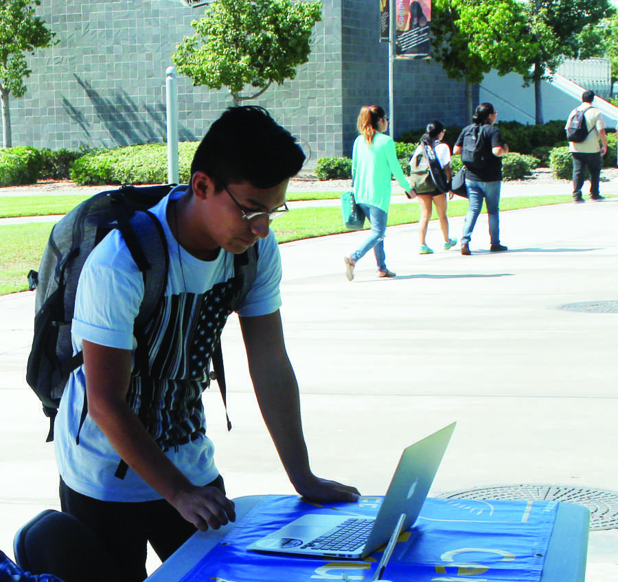 Juan Herrera registers to vote online after talking to the Social Equality Club. The group is hoping to register students in time for them to vote for the elections in November Photo credit: Daniel Green