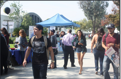 Fair: Students walked down the library sidewalk during the Job Fair on Tuesday. It was organzied by Career Services, hosting companies like Chipotle and FedEx.